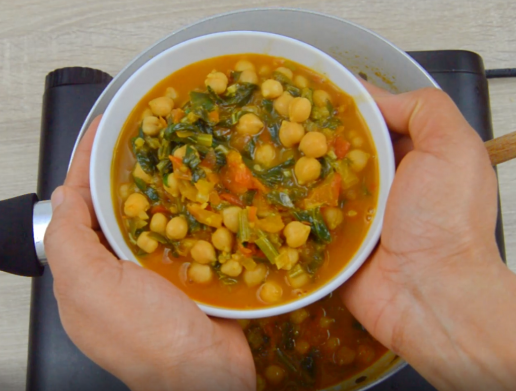 holding a white bowl of chickpea spinach curry.