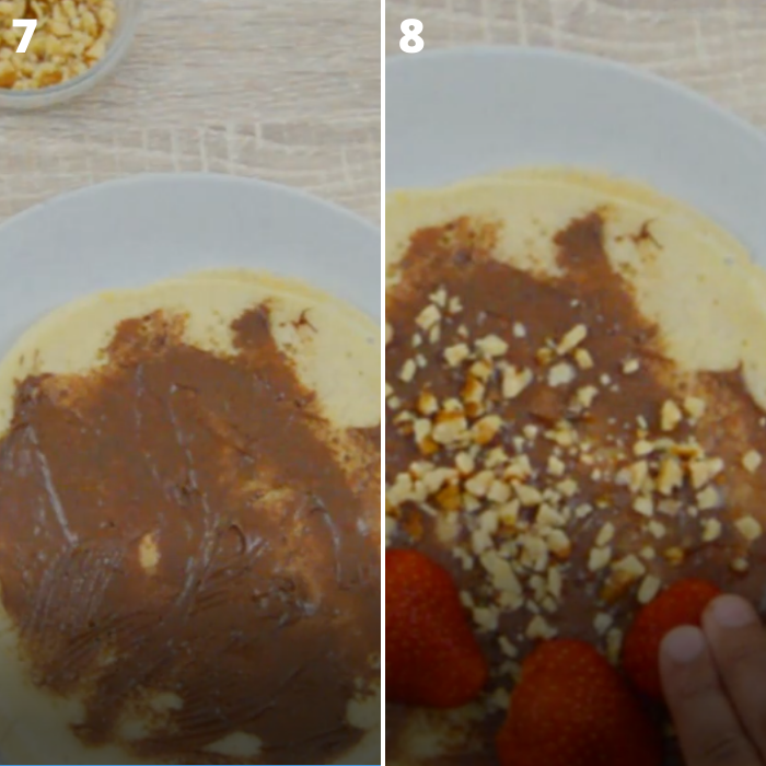 crepes filled with chocolate, nuts and strawberries in a grey plate on a table.