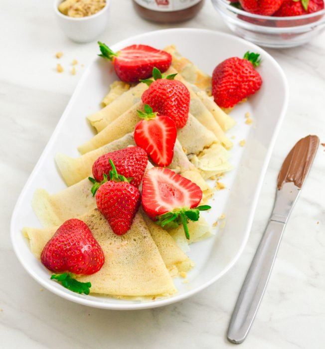 sweet crepes arranged in a white plate with strawberries on top and a knife with chocolate placed on marble.