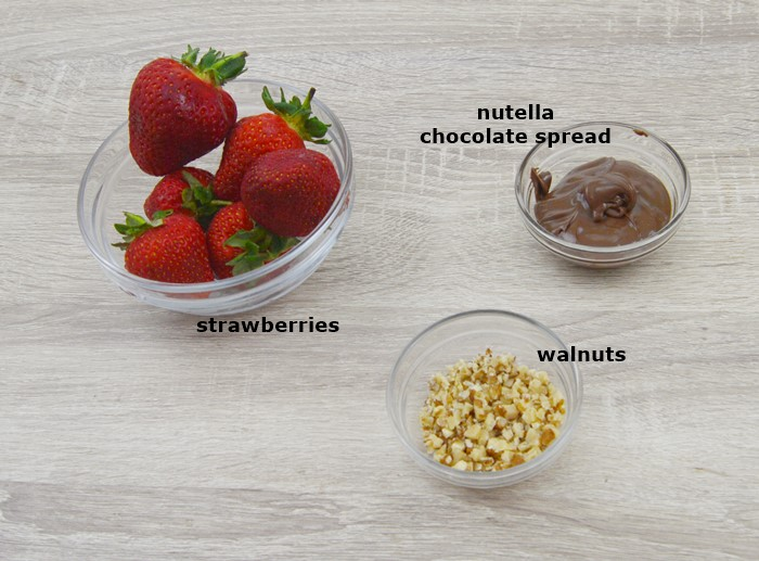 fresh strawberries, chopped walnuts and chocolate spread in individual bowls placed on a table.