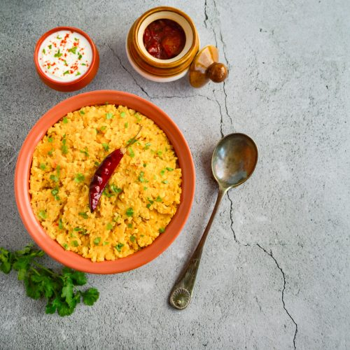 khichdi in a brown bowl placed on a granite along with twigs of coriander, serving spoon, a bowl of yogurt and bowl of pickle.