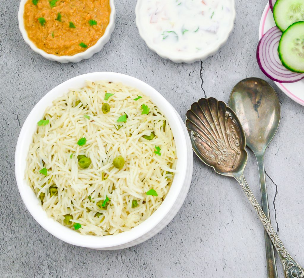 peas pulao in a white bowl placed on a granite along with a bowl of gravy, raita, sliced onion and 2 spoons.