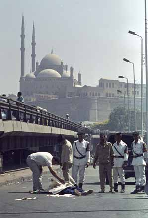 Egypt police stand over a body of a slain terrorist, killed in a failed assassination attempt on a judge hearing extremist cases in Cairo. The Mohammed Ali mosque, a Cairo landmark can be seen in the background. 18th of July 1993. Ph. Norbert Schiller