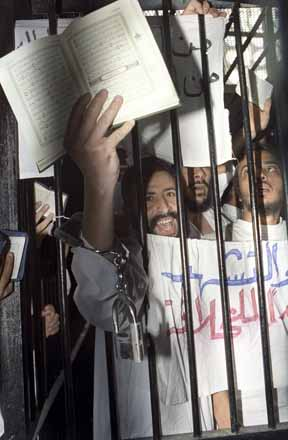 An Islamist, still wearing handcuffs, holds open the Koran from behind the bars inside a military court in Cairo. 15th of August 1993. Ph. Norbert Schiller