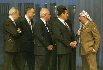 PLO Chairman Yasser Arafat stands apart as (from L to R) Israeli Foreign Minister Shimon Perez, Russian Foreign Minister Andre Kozyrev,  Israeli Prime Minister Yitzhak Rabin and Egyptian President Hosni Mubarak try and persuade Arafat to sign the Cairo document after a dispute broke out over the map marking the boundaries of Jericho.  4th of  May, 1994. Ph. Norbert Schiller