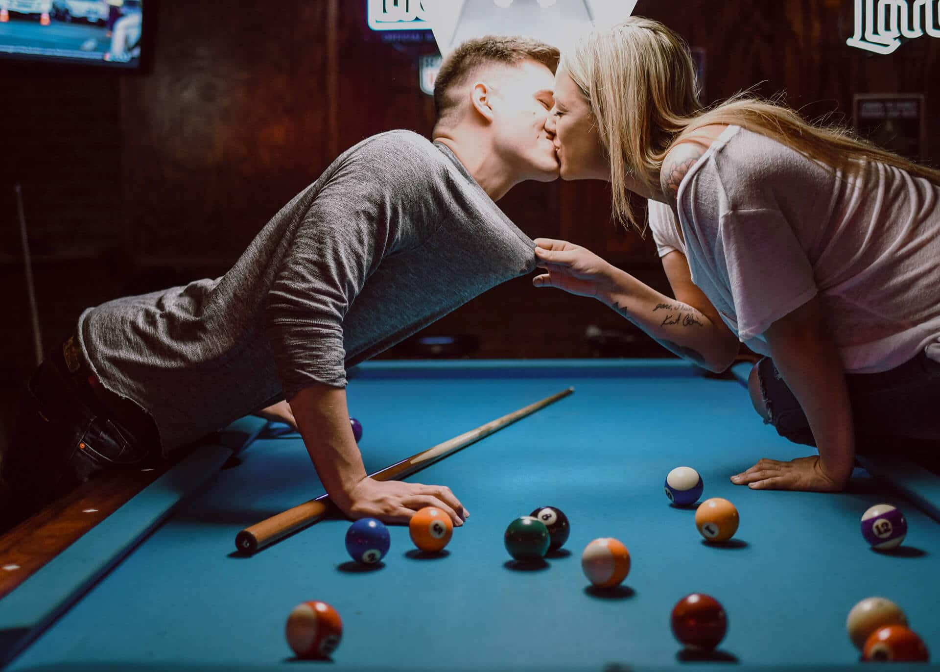 couple kissing over pool table