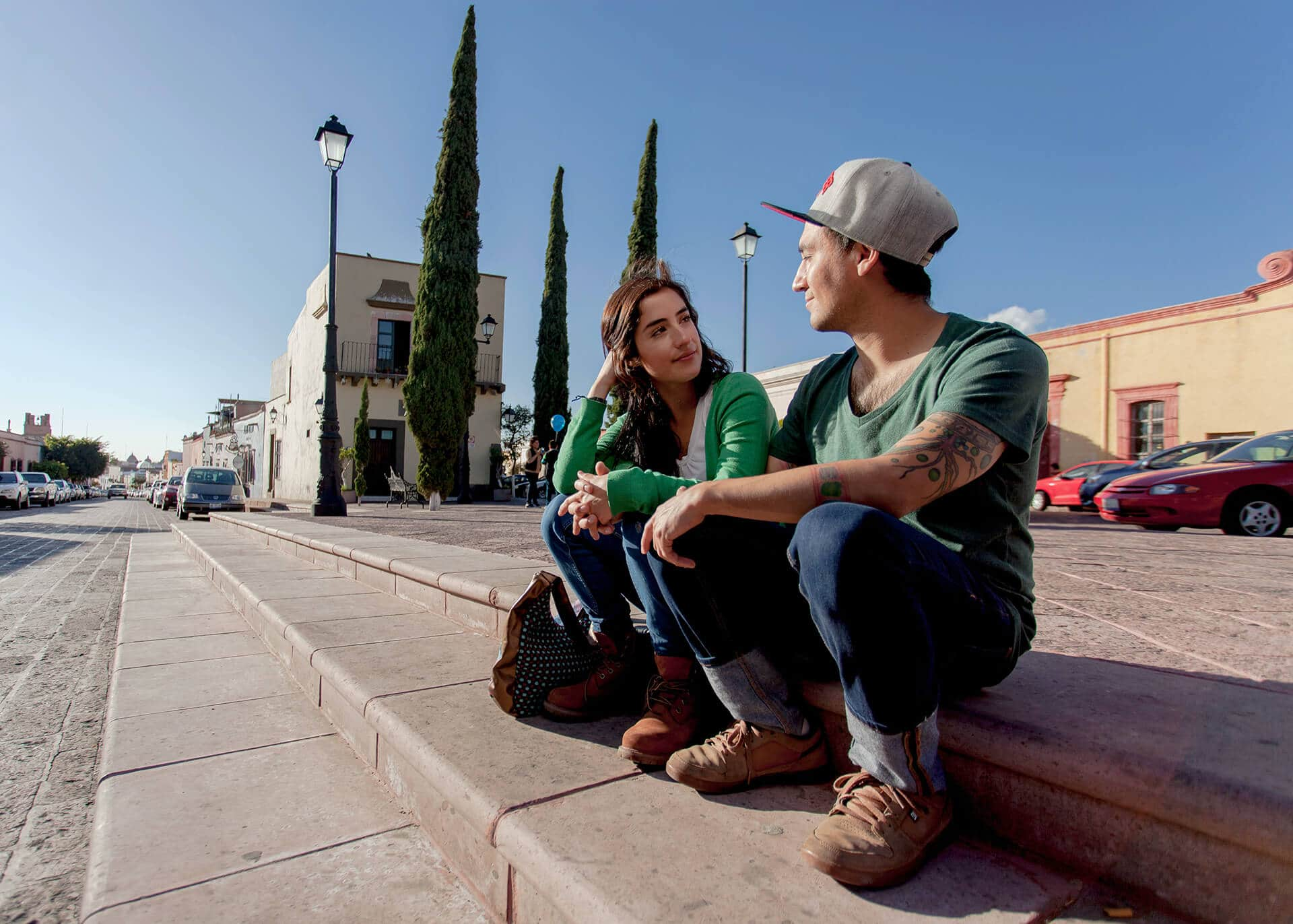 young couple sitting on a curb chatting