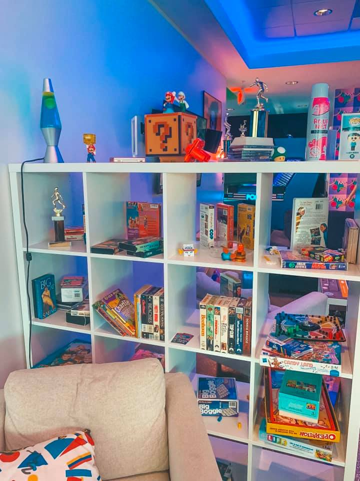Cubbies filled and topped with video game parts, lava lamps, VHS tapes, and board games