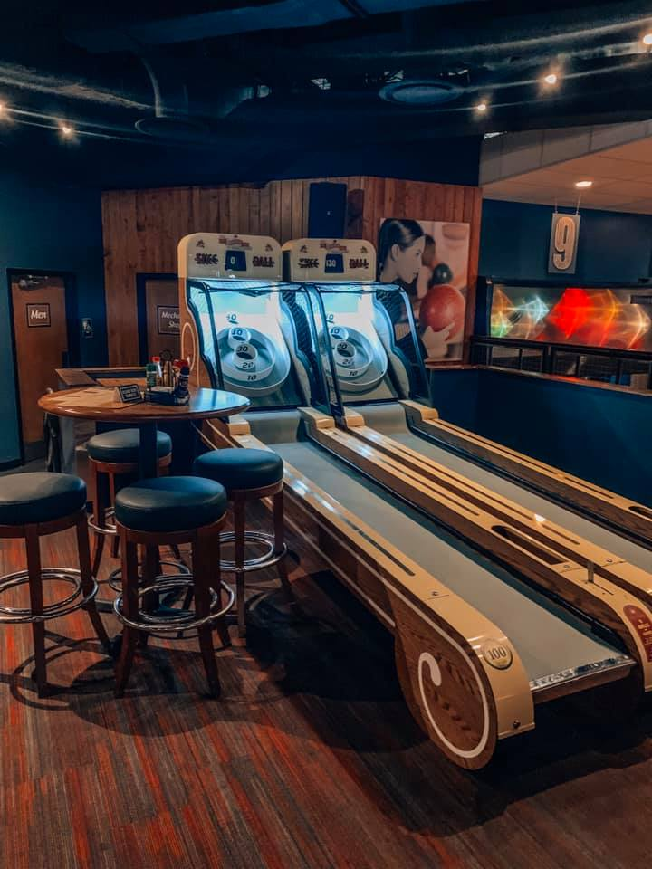 high top seating area next to two skeeball machines