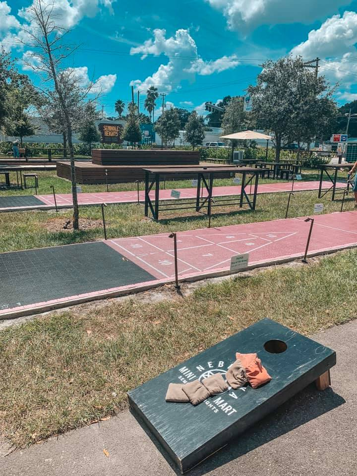 A sunny day with an outdoor setup of corn hole and shuffleboard