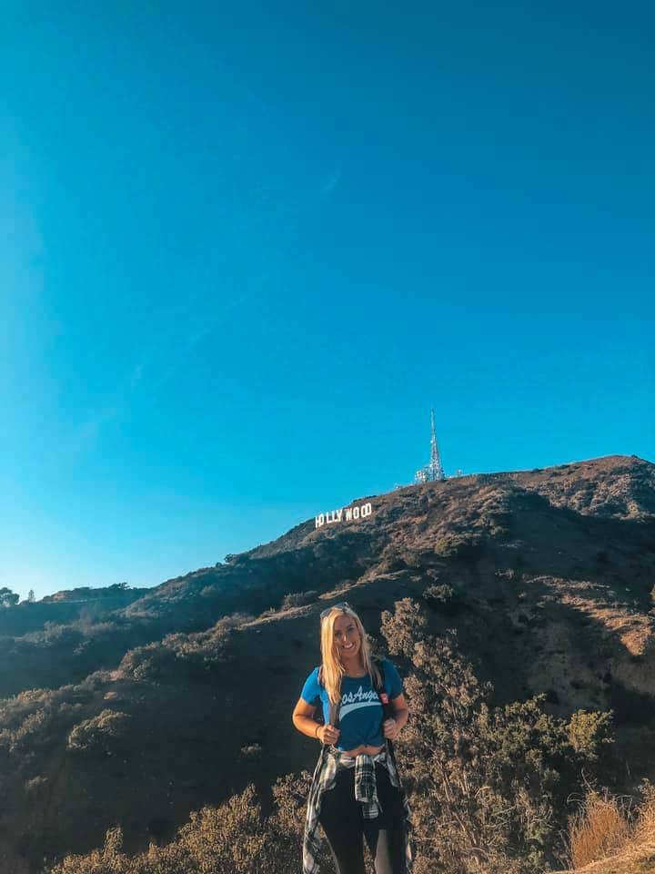 Female solo traveler standing in front of Hollywood sign in Los Angeles