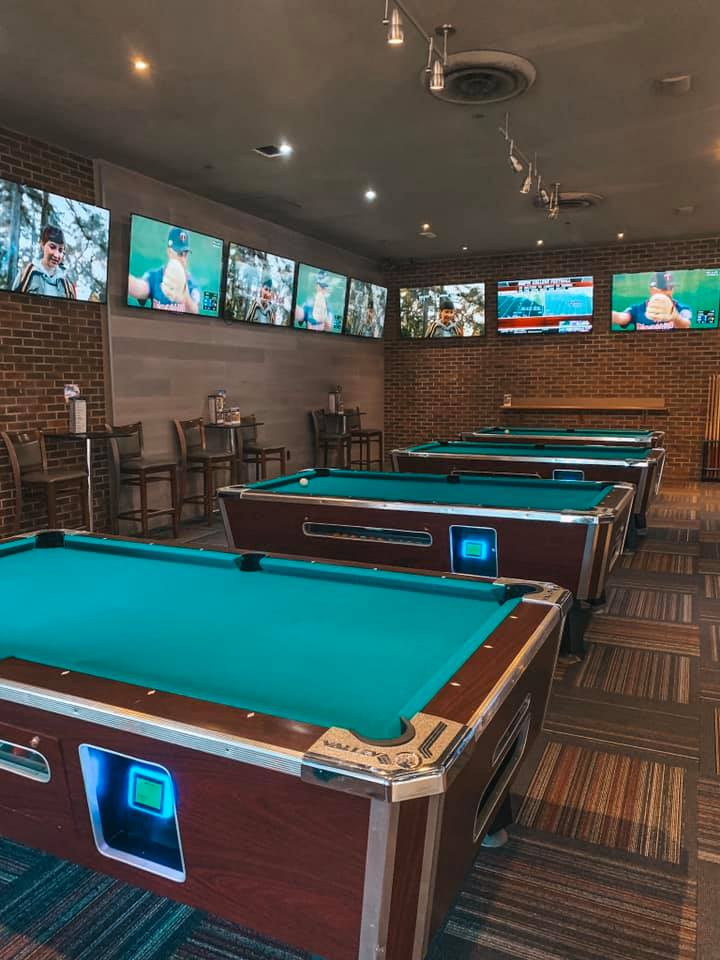 three pool tables surrounded by several tvs airing football games