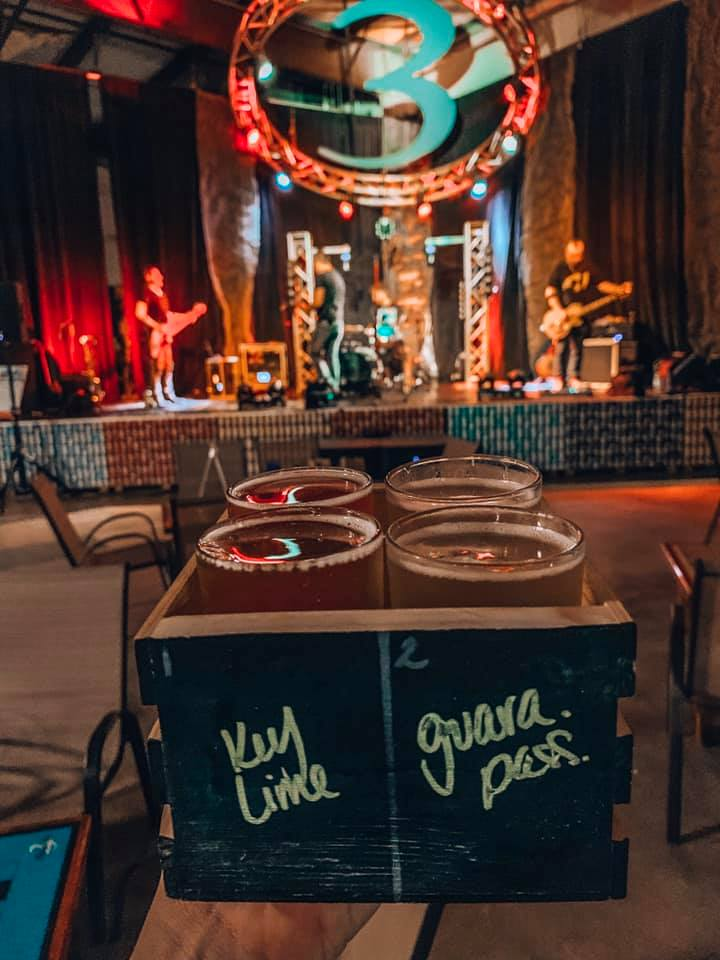 Cider flight held up in front of the stage located in 3 Daughters