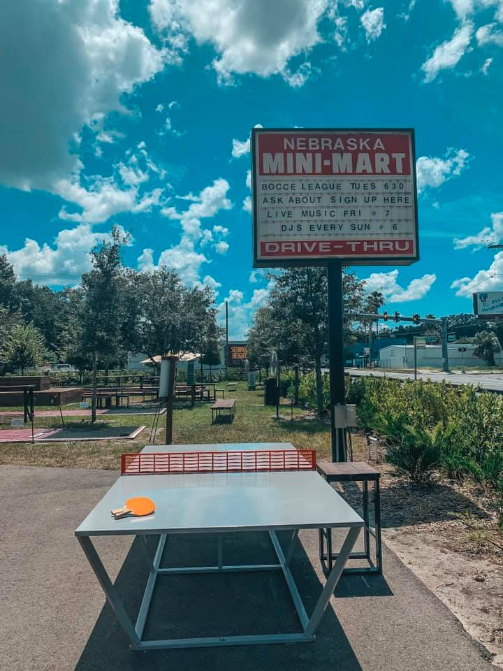 Nebraska Mini Mart sign with an outdoor ping pong table