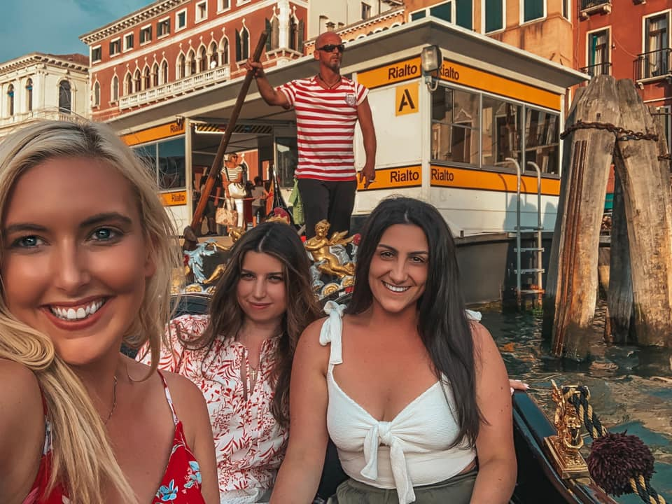 Three girls taking a selfie in a gondola in Venice, Italy. Meeting friends while traveling alone