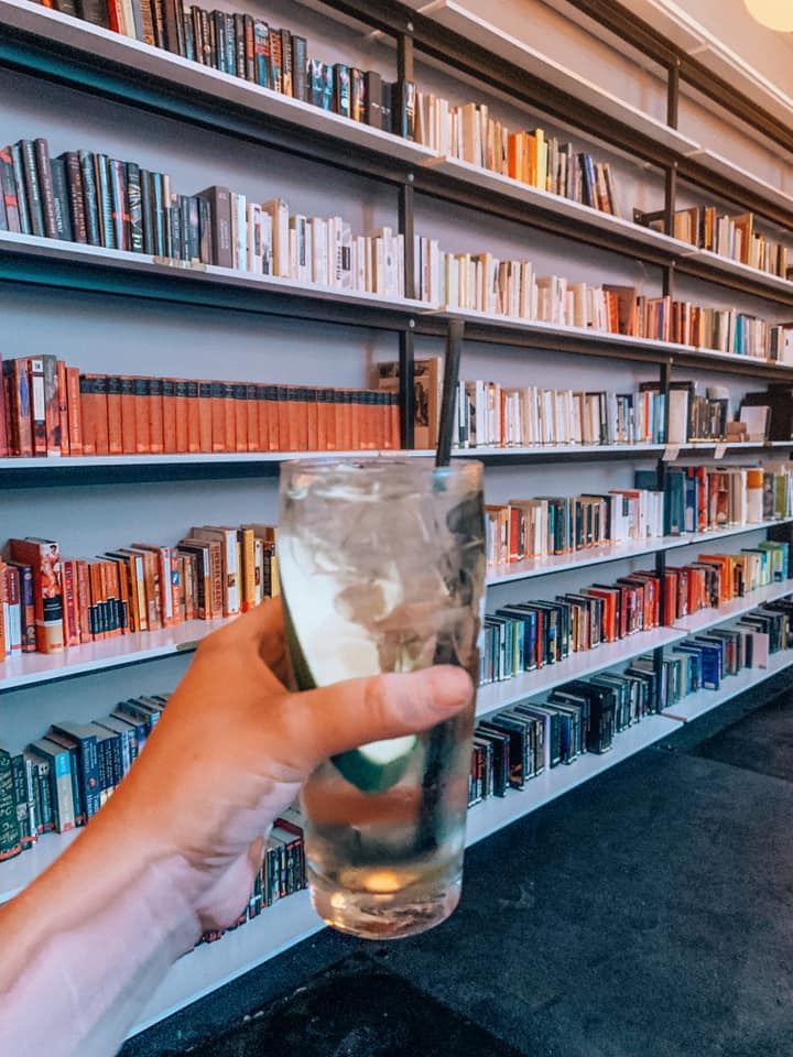 a woman holding a drink in front of a colorful rainbow coordinated bookshelf