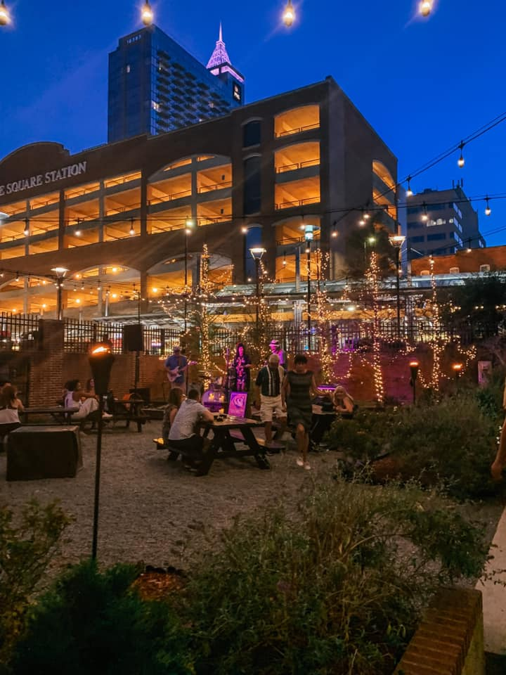 outdoor part of bar watts & ward with string lights and a view of downtown raleigh