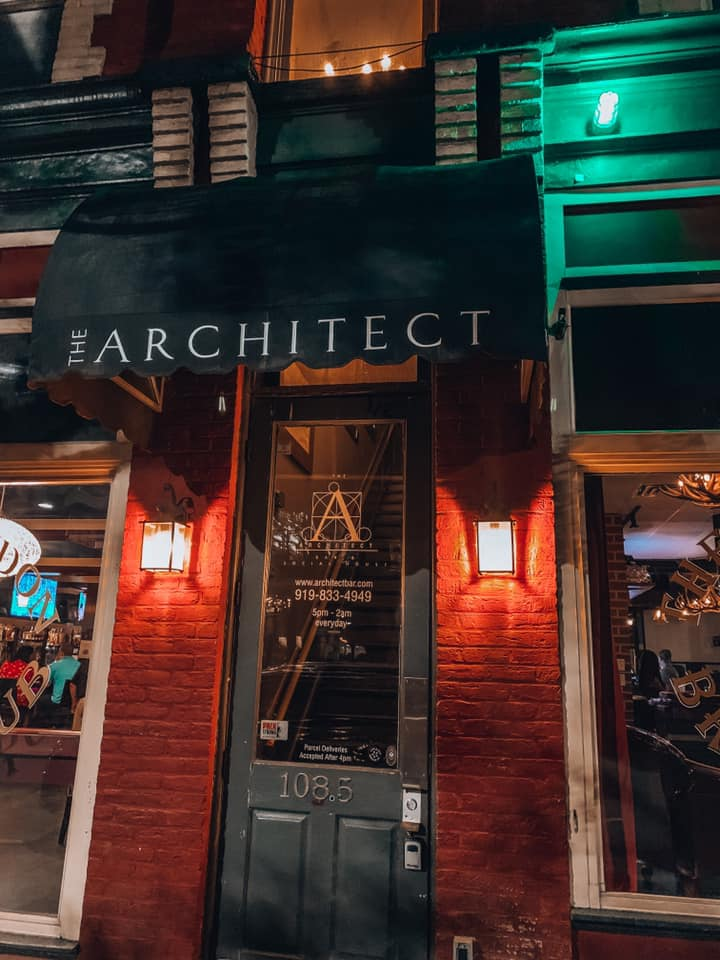 """awning that says """"The Architect"""" with a green light turned on next to it"""