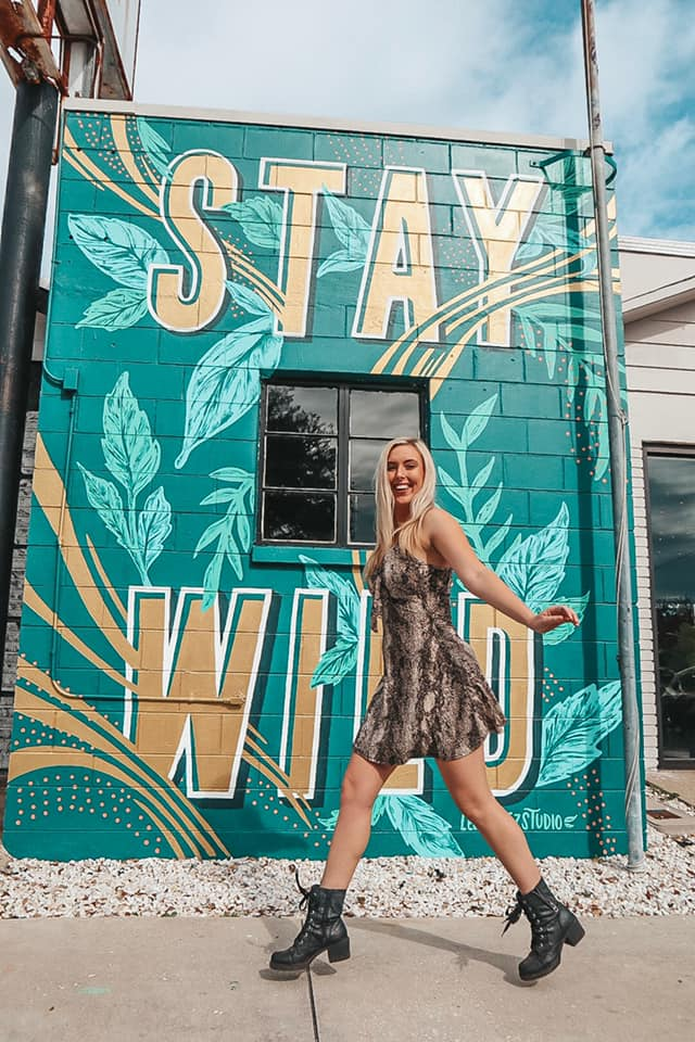 """Jumping in a cheetah dress in front of a mural that says """"Stay Wild"""""""