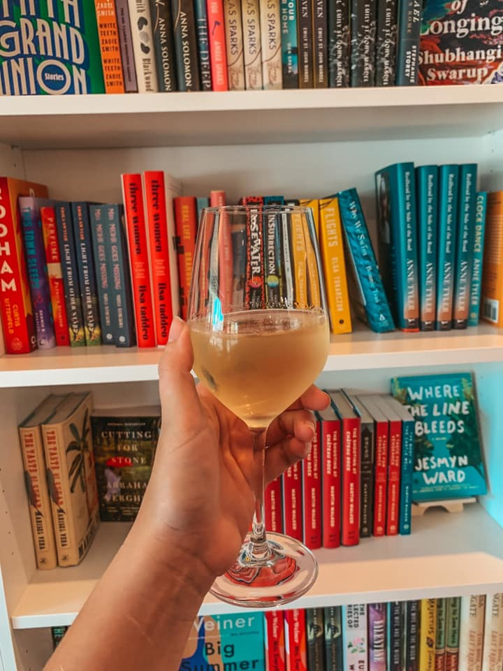 Glass of book + bottle's pinot grigio in front of some of their book selection