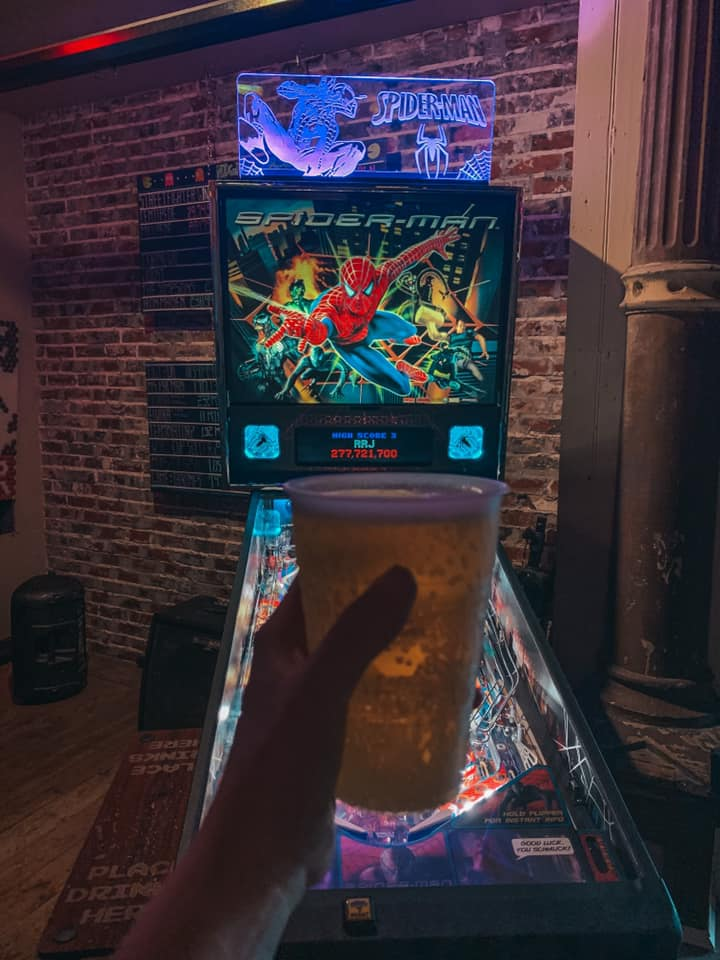 Beer being held in front of pinball machine at Lowry Parcade