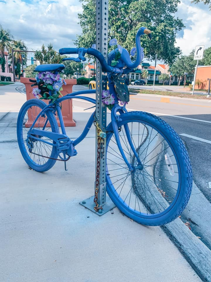 Purple painted bicycle locked up to a street sign