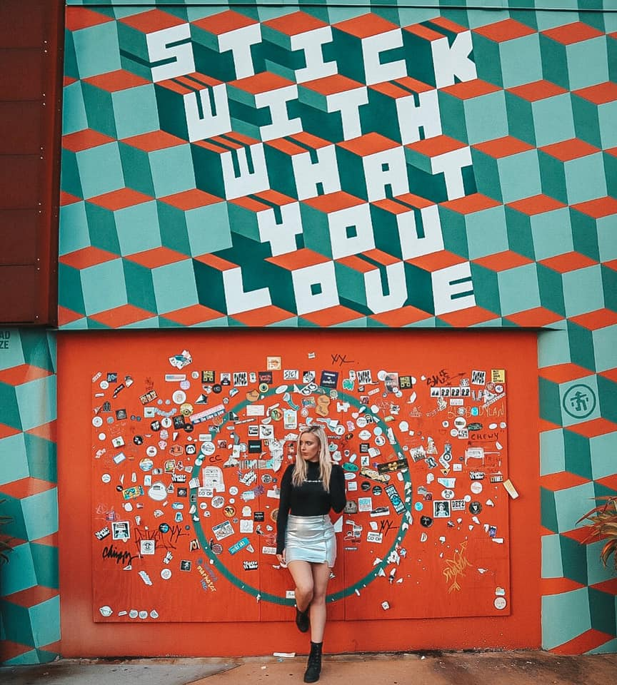 """Woman leaning up against a mural in downtown St. Pete that says """"Stick with what you love"""""""