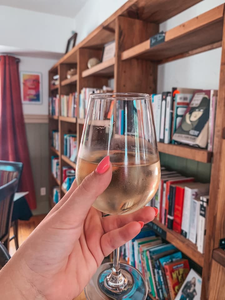 Glass of white wine held up in front of books at The Reserve