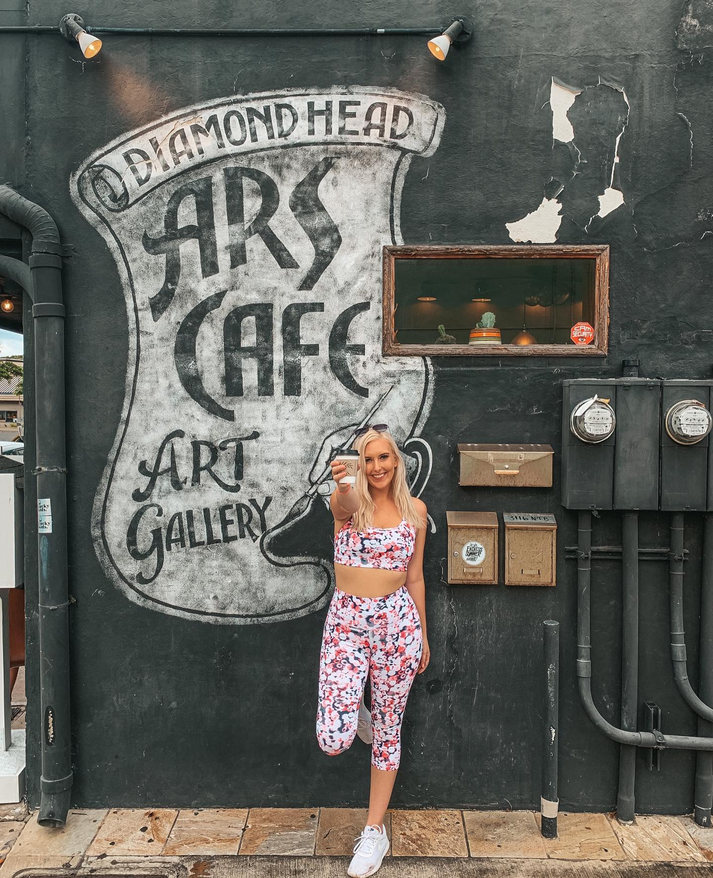 """Destiny wearing a pink speckled workout outfit and holding up coffee outside of Ars Cafe in front of their mural that reads """"Diamond Head Ars Cafe Art Gallery"""""""