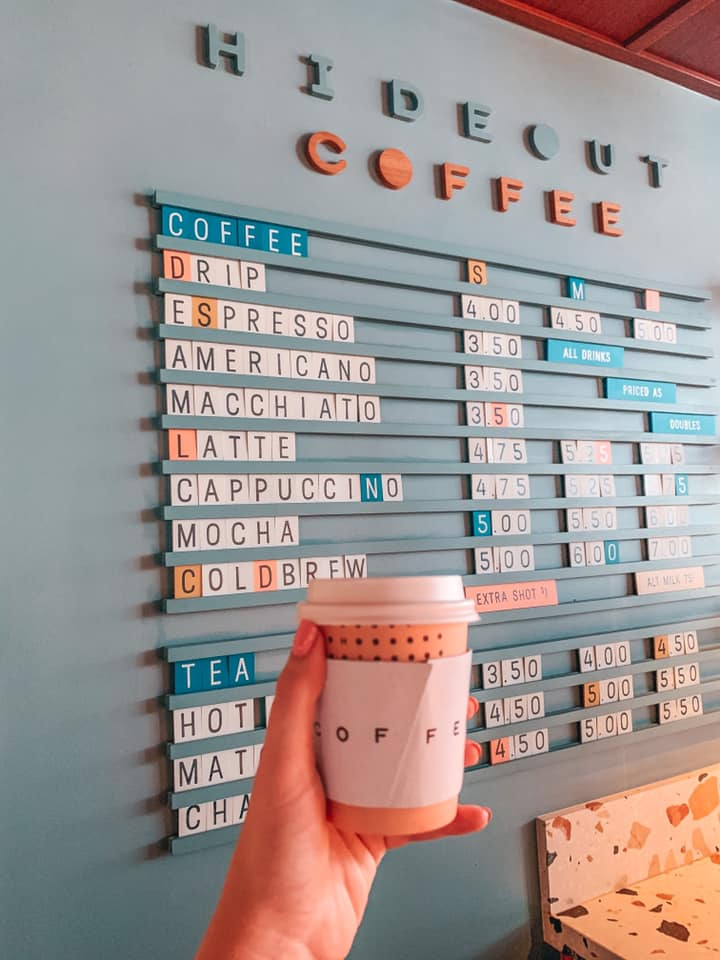 Holding up coffee cup in front of the menu at Hideout Coffee