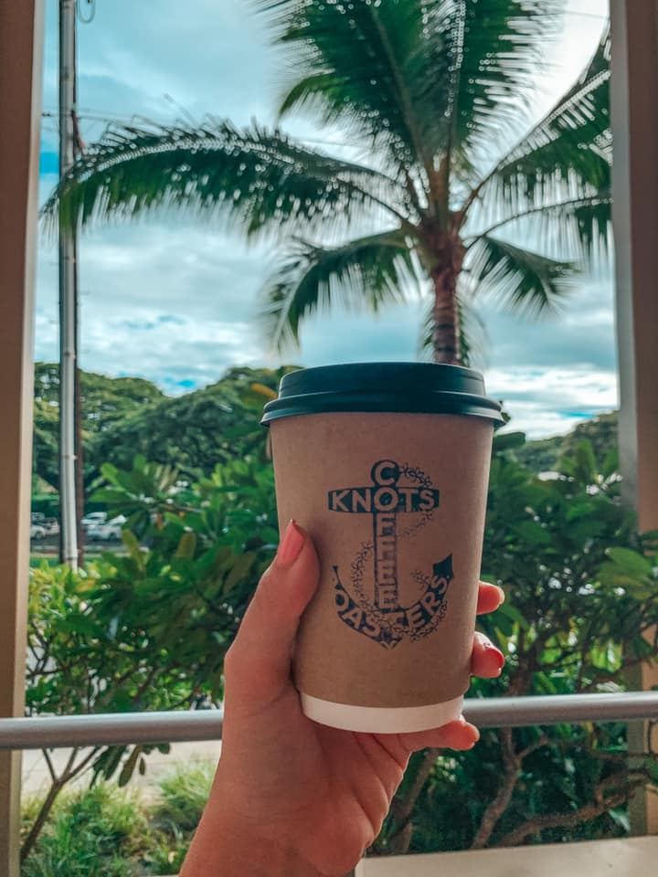 Holding up Knots Coffee cup in front of a palm tree