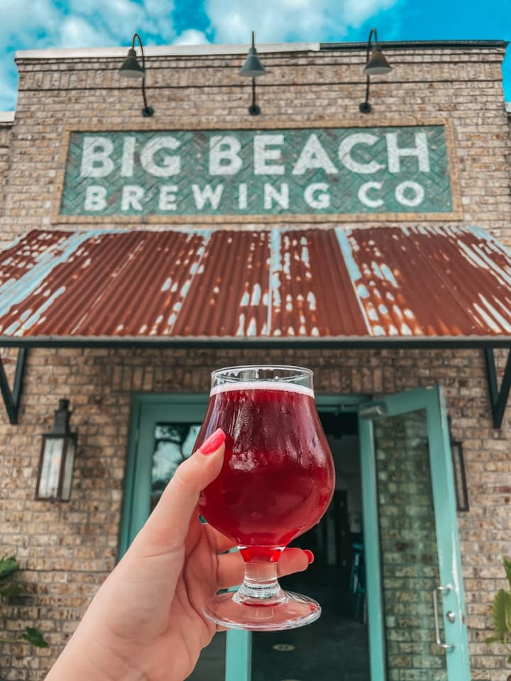 Holding up Fruiturama sour in front of Big Beach Brewing Co entrance
