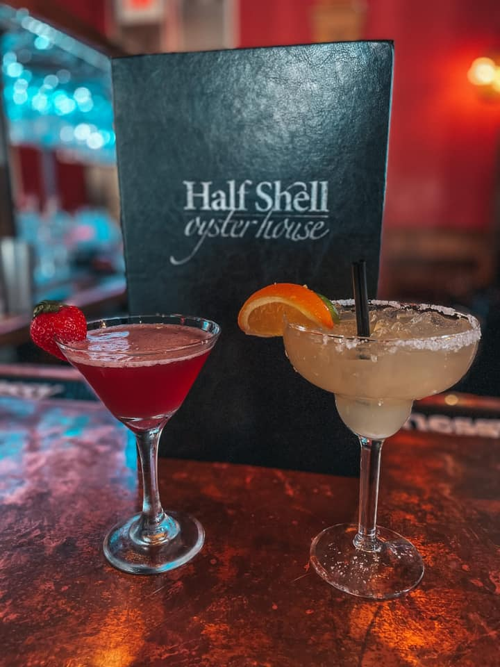 Martini and margarita in front of Half Shell Oyster House menu