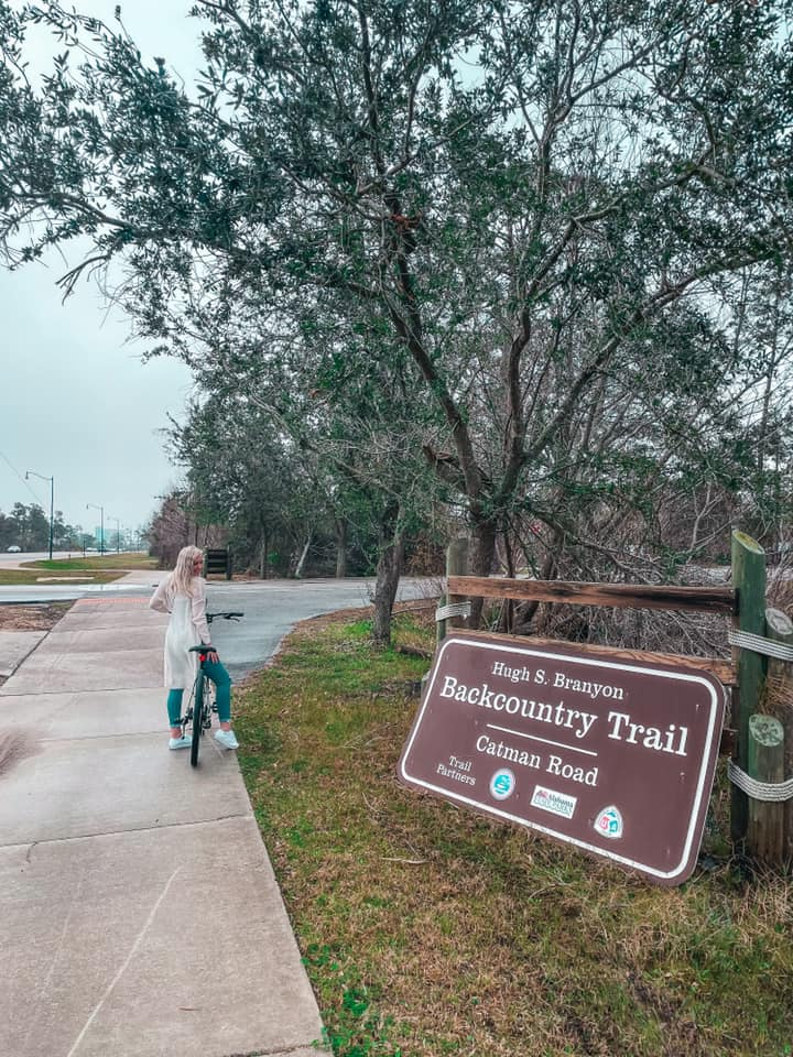 Sitting on bicycle in front of trail sign for the Hugh S Branyon Trail at Gulf State Park in Orange Beach, Alabama