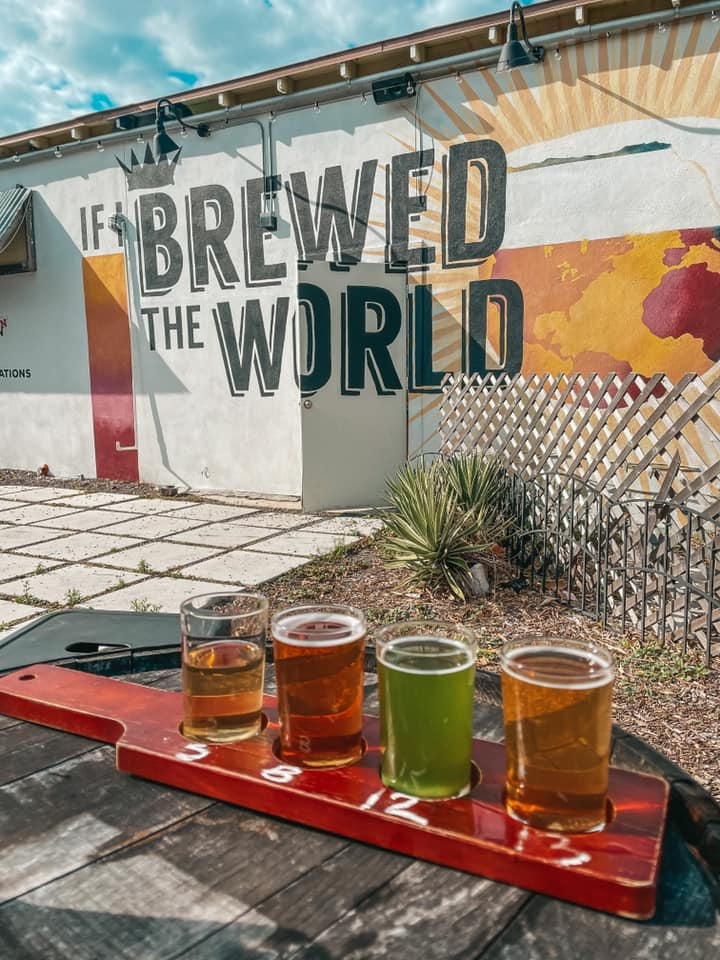 """Beer flight on the patio in front of """"If I brewed the world"""" mural"""
