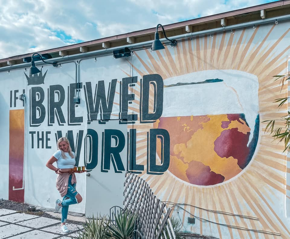 """Holding beer flight in front of """"If I brewed the world"""" mural"""