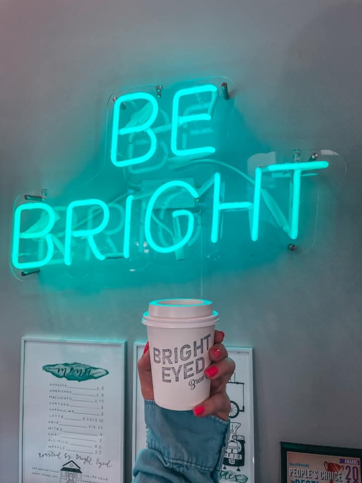 """Holding up coffee from bright eyed brew co in front of a neon sign that reads """"be bright"""""""