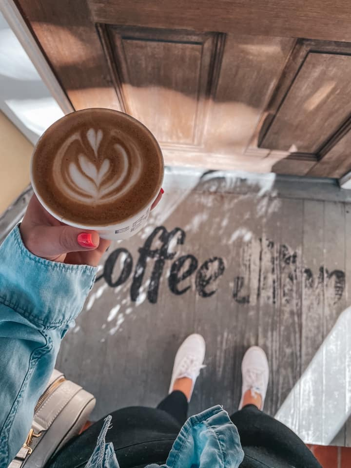 """holding latte with fun design over doorstep area that reads """"coffee stop"""""""