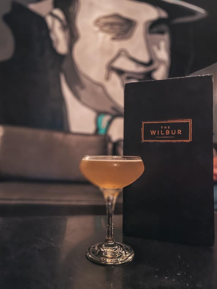 Cocktail from The Wilbur in front of menu and Al Capone art in the background