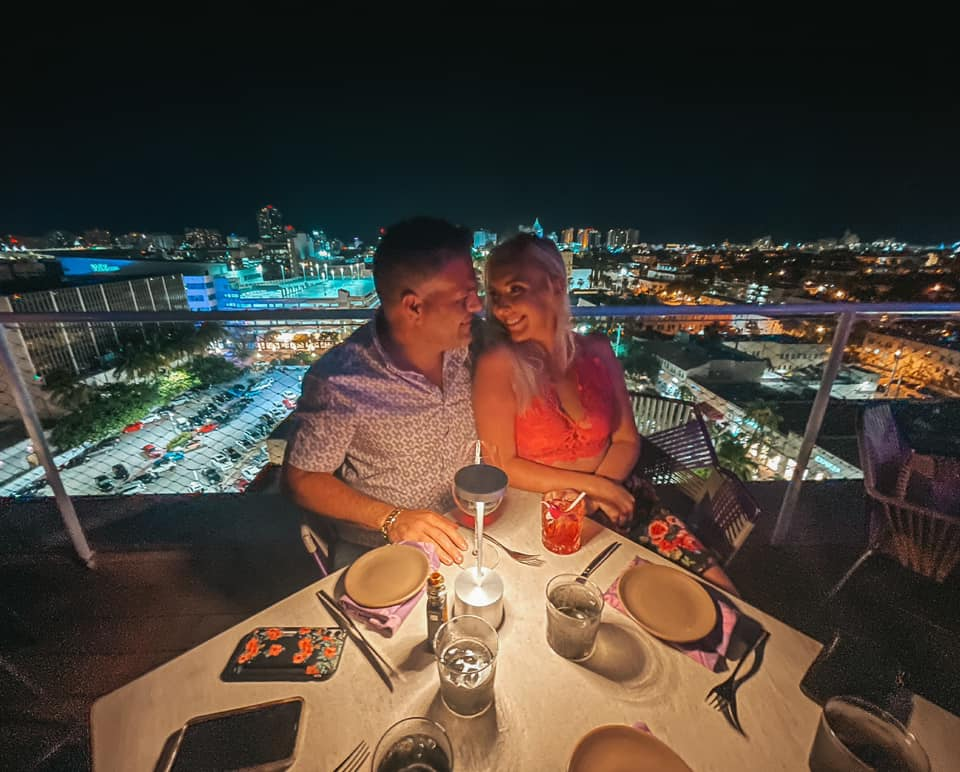 Couple enjoying cocktails and night views from Juvia rooftop in Miami