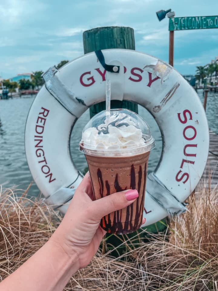 Frozen coffee drink with Gypsy Souls sign and inter coastal views