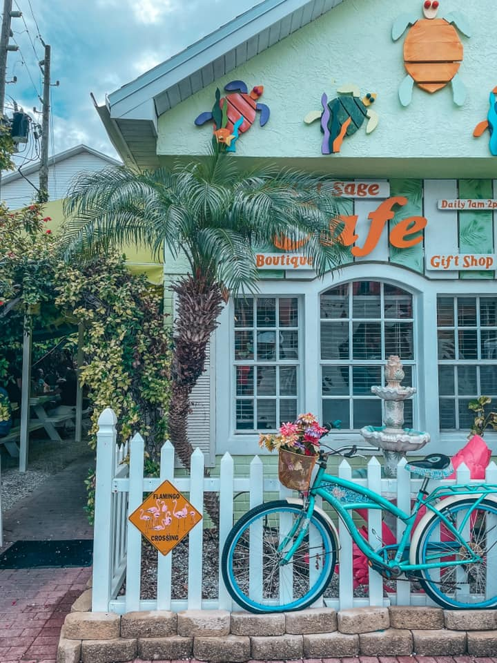 Sweet Sage Cafe entrance with a bike parked along a white picket fence