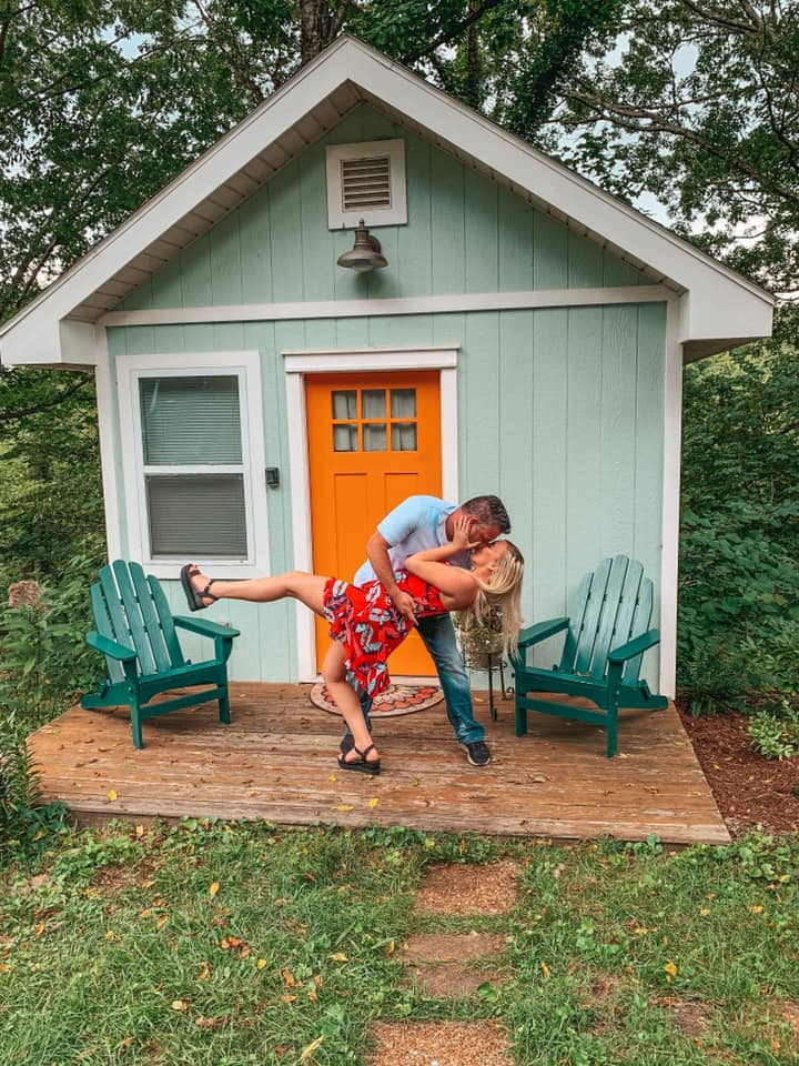 Man dipping and kissing a woman in front of a tiny home in Asheville
