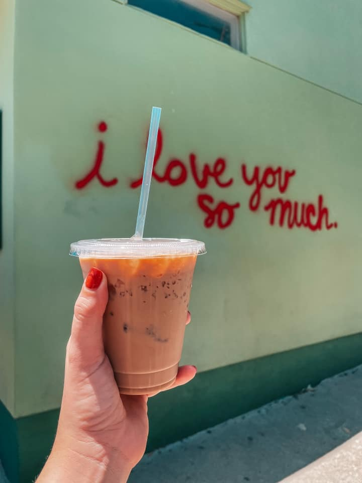 Holding up Jo's Coffee in front of I love you so much one of the things to Do in Austin