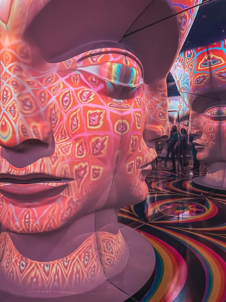 Trippy, colorful room, with giant head and mirrors inside of Meow Wolf