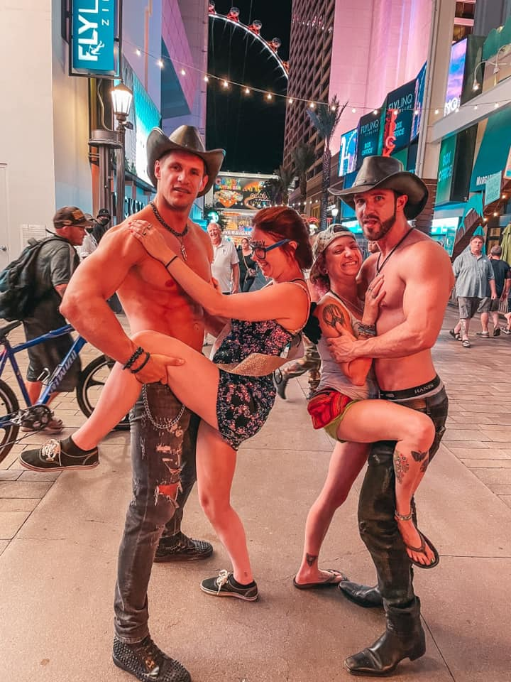 Two women posing with two men in cowboy hats on The Strip in Vegas