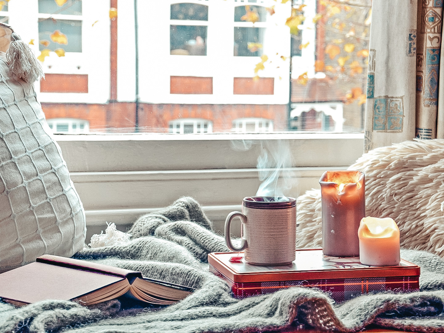 cozy home with candles, books, and coffee after moving to a city alone