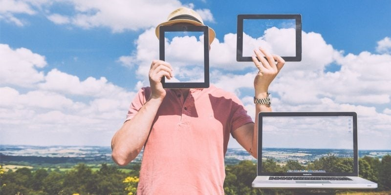 Photo of man holding tablet over his face and in the air, with laptop next to him all showing photos of the landscape directly behind them
