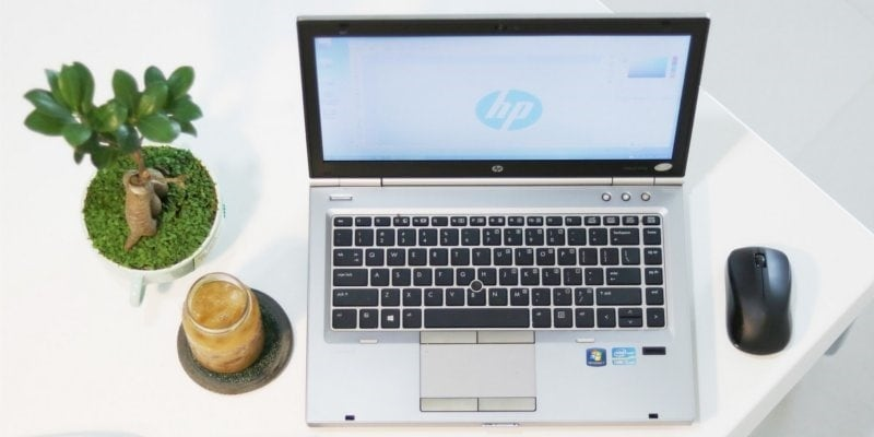 Photo of minimalist hp laptop with bonsai tree, candle and mouse against white background