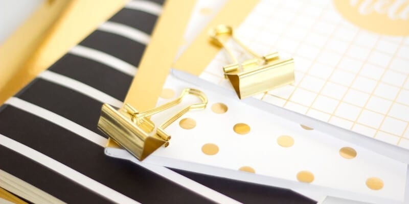The best tools for bloggers images header image of black and gold notbooks and paper clips